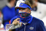 Florida head coach Dan Mullen, right, pauses during a timeout against Georgia during the second half of an NCAA college football game, Saturday, Nov. 7, 2020, in Jacksonville, Fla. No. 6 Florida doesn't really even try to run the ball anymore. There's an occasional handoff here and there, but the Gators are mostly one-dimensional _ and that's fine with coach Dan Mullen, Heisman Trophy front-runner Kyle Trask and arguably the deepest receiving corps in the country. (AP Photo/John Raoux)