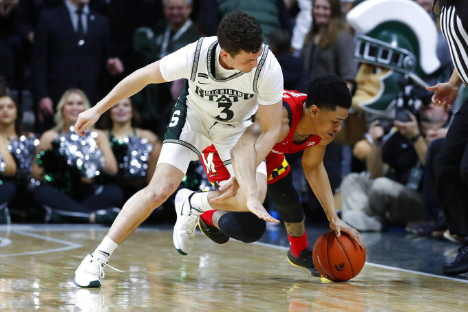 Michigan State guard Foster Loyer (3) fouls Maryland guard Anthony Cowan Jr. (1) during a loose ball in the first half of an NCAA college basketball game in East Lansing, Mich., Saturday, Feb. 15, 2020. (AP Photo/Paul Sancya)