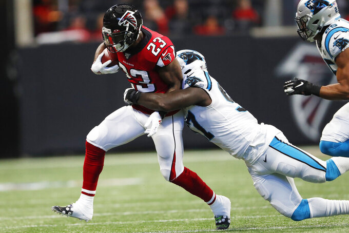 Carolina Panthers linebacker Mario Addison (97) tackles Atlanta Falcons running back Brian Hill (23) during the first half of an NFL football game, Sunday, Dec. 8, 2019, in Atlanta. (AP Photo/John Bazemore)