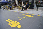 Customers sit in the outdoor seating of bars and cafes in Cardiff prior to Wales entering a