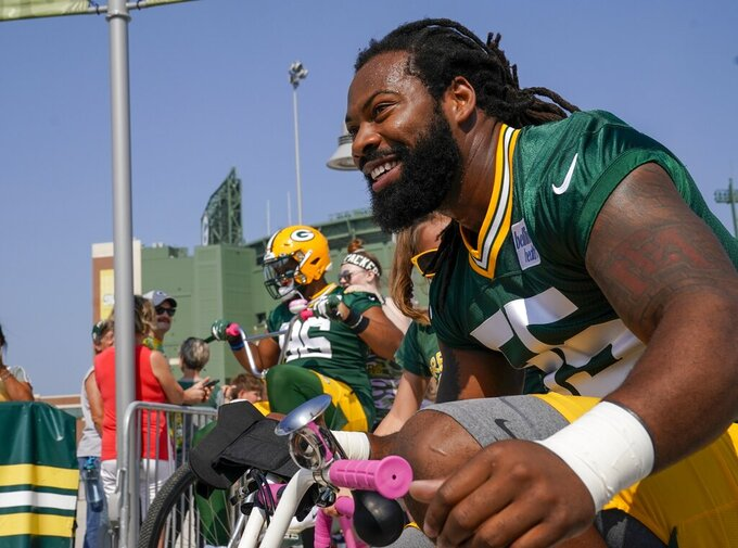 Green Bay Packers' Za'Darius Smith (55) and Kingsley Keke ride bikes to NFL football training camp Thursday, July 25, 2019, in Green Bay, Wis. (AP Photo/Morry Gash)