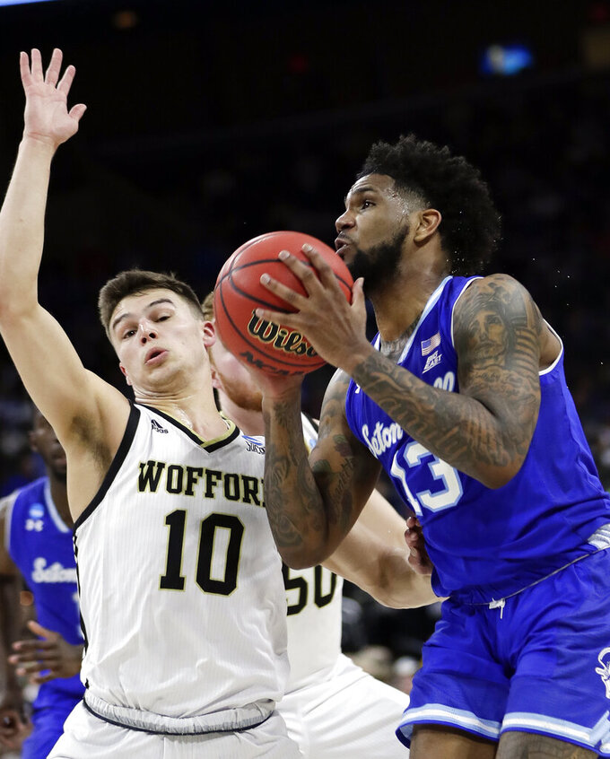 Seton Hall's Myles Powell, right, goes up for shot past Wofford's Nathan Hoover (10) during the first half of a first-round game in the NCAA men's college basketball tournament in Jacksonville, Fla., Thursday, March 21, 2019. (AP Photo/John Raoux)