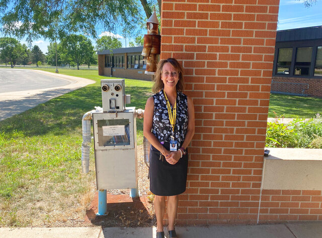 Longfellow Elementary School principal Amy Adams poses in front of two robots that greet her students every morning outside of the school in Rochester, Minn., on Thursday, July 30, 2020. Her school started earlier this month, and she says keeping kids in masks and distanced has been a challenge - but that the kids are getting used to it. (Catharine Richert/Minnesota Public Radio via AP)
