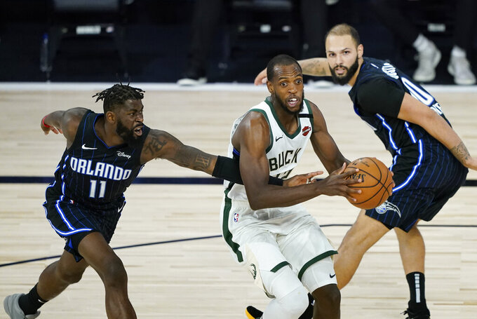 Milwaukee Bucks' Khris Middleton drives past Orlando Magic's James Ennis III (11) during the second half of an NBA basketball first round playoff game Monday, Aug. 24, 2020, in Lake Buena Vista, Fla. (AP Photo/Ashley Landis, Pool)