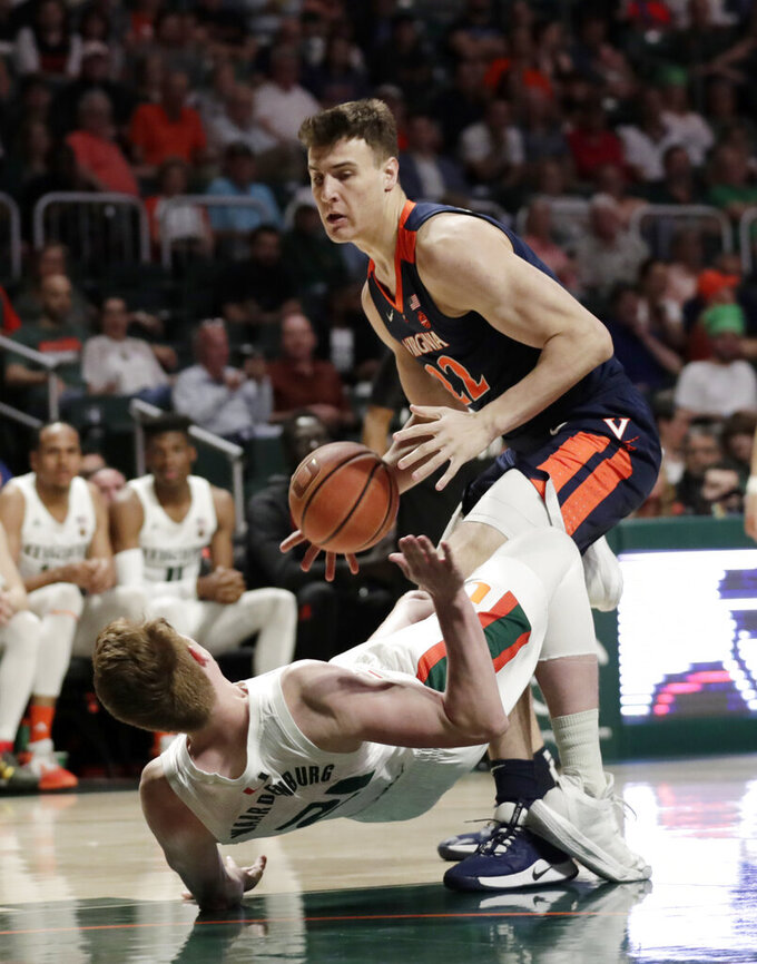 Miami forward Sam Waardenburg (21) falls to the court as he is fouled by Virginia center Francisco Caffaro (22) during the first half of an NCAA college basketball game, Wednesday, March 4, 2020, in Coral Gables, Fla. (AP Photo/Lynne Sladky)