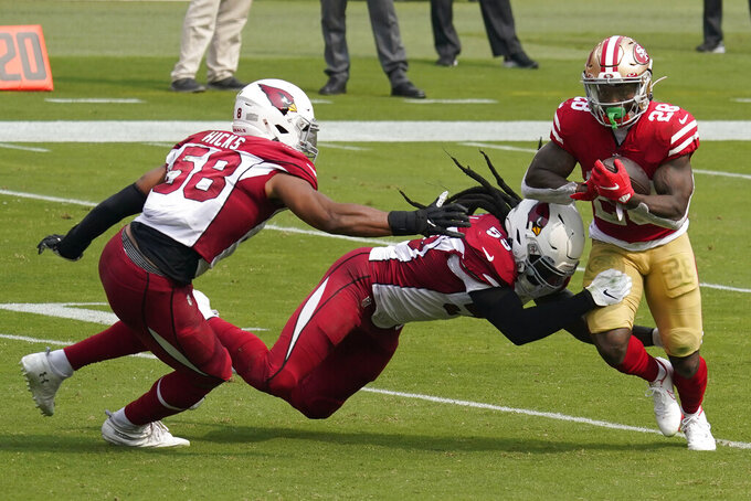 San Francisco 49ers running back Jerick McKinnon (28) runs against Arizona Cardinals middle linebacker Jordan Hicks (58) and outside linebacker De'Vondre Campbell during the first half of an NFL football game in Santa Clara, Calif., Sunday, Sept. 13, 2020. (AP Photo/Tony Avelar)