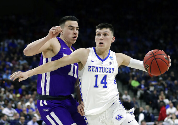 Kentucky's Tyler Herro (14) drives past Abilene Christian's Tobias Cameron (11) during the first half of a first-round game in the NCAA men's college basketball tournament in Jacksonville, Fla. Thursday, March 21, 2019. (AP Photo/John Raoux)