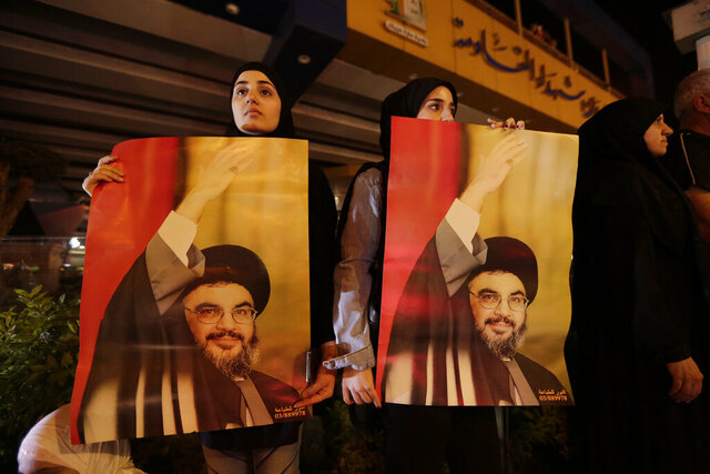 FILE - In this Oct. 25, 2019 file photo, supporters of Hezbollah leader Sayyed Hassan Nasrallah hold his picture, in the southern suburbs of Beirut, Lebanon. Nasrallah has thrown his support behind the Lebanese government seeking financial assistance from the International Monetary Fund but said it should negotiate the conditions cautiously. Nasrallah's comments on Monday, May 4, 2020, came four days after the country's prime minister said Lebanon will seek a rescue deal from the IMF to help the nation find a way out of a crippling financial crisis. (AP Photo/Hassan Ammar, File)
