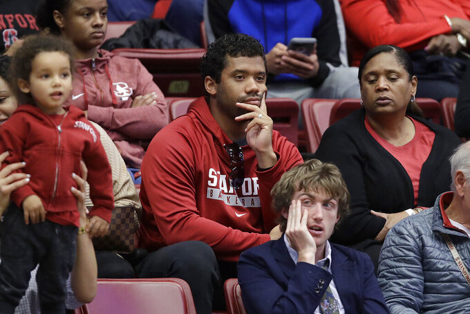 Seattle Seahawks quarterback Russell Wilson, center, watches during the second half of a first-round game in the NCAA women's college basketball tournament between BYU and Auburn in Stanford, Calif., Saturday, March 23, 2019. (AP Photo/Jeff Chiu)