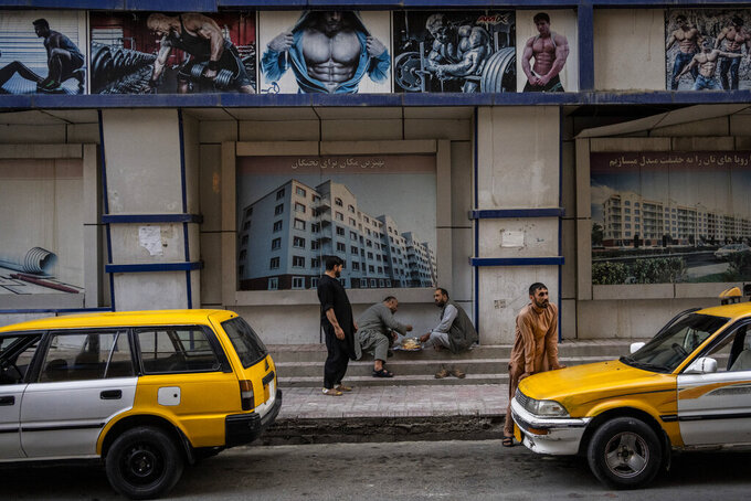 Afghans eat on the street in Kabul, Afghanistan, Saturday, Sept. 11, 2021. (AP Photo/Bernat Armangue)