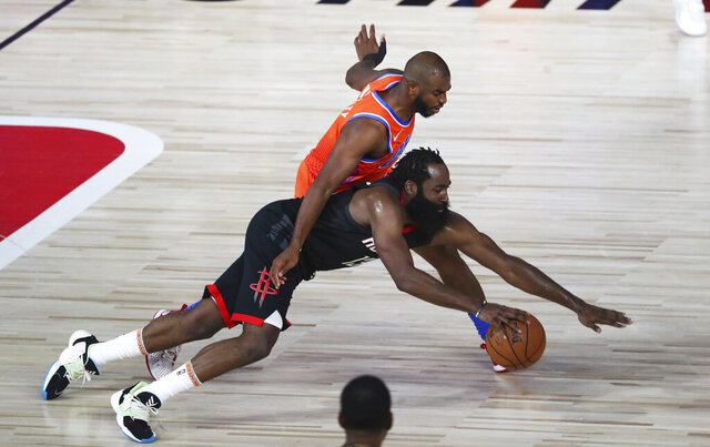 Oklahoma City Thunder guard Chris Paul, top, fouls Houston Rockets guard James Harden during the second half of Game 1 of an NBA basketball first-round playoff series, Tuesday, Aug. 18, 2020, in Lake Buena Vista, Fla. (Kim Klement/Pool Photo via AP)