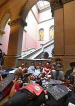 Protesters from VOCAL NY lay on the floor outside the Assembly Chamber urging legislators to pass legalization of Marijuana legislation at the state Capitol Wednesday, June 19, 2019, in Albany, N.Y. (AP Photo/Hans Pennink)
