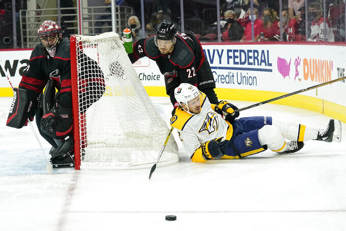 Carolina Hurricanes goaltender Alex Nedeljkovic, left, and defenseman Brett Pesce (22) defend the goal while Nashville Predators center Ryan Johansen (92) falls to the ice during the first period in Game 5 of an NHL hockey Stanley Cup first-round playoff series in Raleigh, N.C., Tuesday, May 25, 2021. (AP Photo/Gerry Broome)