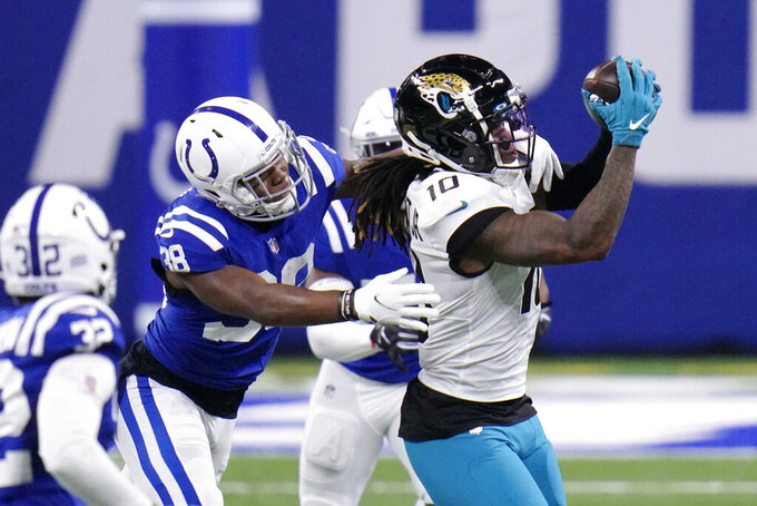 Jacksonville Jaguars' Laviska Shenault Jr. (10) makes a catch against Indianapolis Colts' T.J. Carrie (38) during the first half of an NFL football game, Sunday, Jan. 3, 2021, in Indianapolis. (AP Photo/AJ Mast)