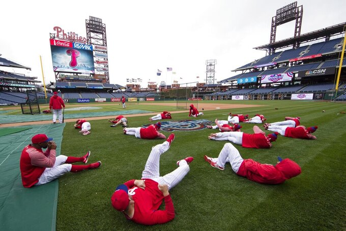 FILE - In this April 7, 2017, file photo, members of the Philadelphia Phillies stretch before the team's baseball game against the Washington Nationals in Philadelphia. Five players for the Philadelphia Phillies have tested positive for COVID-19 at the team's spring camp in Florida, prompting the club to indefinitely close the complex. The team also said Friday, June 19, 2020, that three staff members at the camp have tested positive. The club didn't identify any of those affected. (AP Photo/Matt Rourke, File)