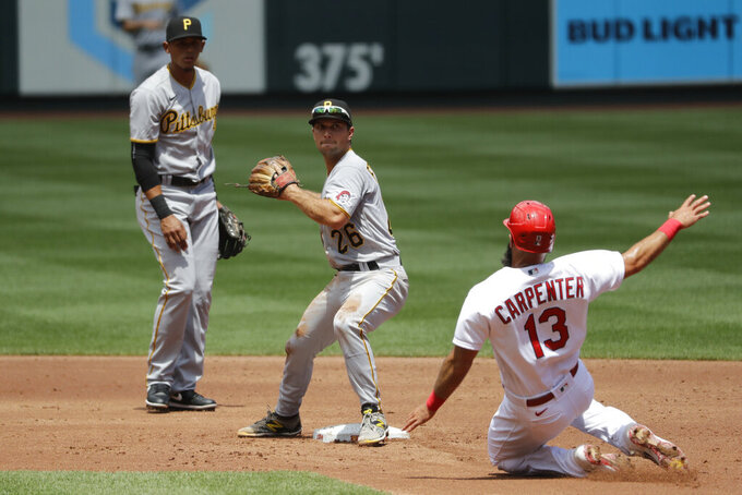 St. Louis Cardinals' Matt Carpenter (13) is out at second as Pittsburgh Pirates second baseman Adam Frazier turns the double play and Pirates shortstop Erik Gonzalez, left, watches during the second inning of a baseball game Sunday, July 26, 2020, in St. Louis. The Cardinals' Yadier Molina was out at first. (AP Photo/Jeff Roberson)