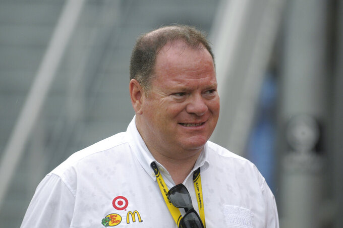 """FILE - NASCAR car owner Chip Ganassi walks back to the garage area during a rain delay at the Coke Zero 400 auto race at Daytona International Speedway in Daytona Beach, Fla., in this Saturday, July 3, 2010, file photo. Chip Ganassi has sold his NASCAR team to Justin Marks, owner of Trackhouse Racing, and will pull out of the nation's top stock car series at the end of this season. Ganassi fields two cars in the Cup Series but will transfer his North Carolina race shop and all its assets to Marks for 2022. """"He made me a great offer that required my attention,"""" Ganassi told The Associated Press on Wednesday, June 30, 3031, as the sale was announced. (AP Photo/Phelan M. Ebenhack, File)"""