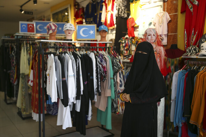 Munire Bugra, 35, a member of the Uighur community, stands in a clothes shop in Istanbul's Zeytinburnu neighborhood, Tuesday, Feb. 2, 2021. Because of shared cultural ties, Turkey has long been a safe haven for the Uighurs, a Turkic group native to China's far west Xinjiang region. Bugra says many in the community are anxious they may be deported back to China amid allegations of an exchange of her compatriots for coronavirus vaccines. (AP Photo/Emrah Gurel)