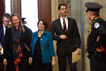 Sen. Amy Klobuchar, D-Minn., third from left, and Sen. Tom Cotton, R-Ark. forth from left, arrive at the Capitol in Washington, Tuesday, Jan. 21, 2020. President Donald Trump's impeachment trial quickly burst into a partisan fight Tuesday as proceedings began unfolding at the Capitol. Democrats objected strongly to rules proposed by the Republican leader for compressed arguments and a speedy trial. (AP Photo/Julio Cortez)