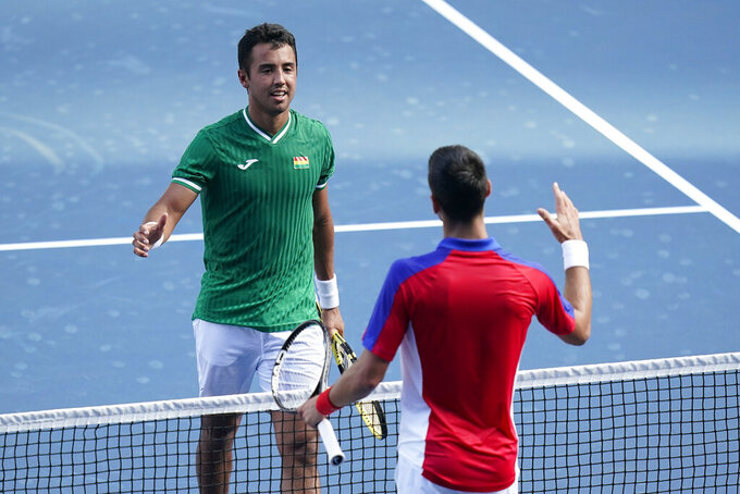 Hugo Dellien, left, of Bolivia, speaks with Novak Djokovic, of Serbia, after losing to Djokovic during the tennis competition at the 2020 Summer Olympics, Saturday, July 24, 2021, in Tokyo, Japan. (AP Photo/Patrick Semansky)
