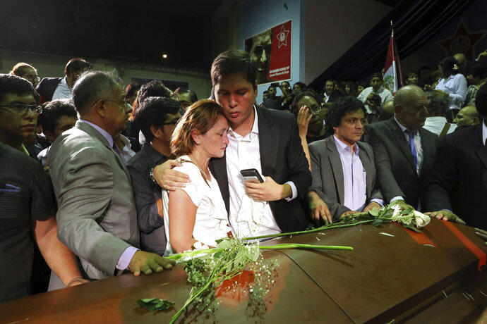 People embrace by the coffin of former President Alan Garcia during his wake at his party's headquarters in Lima, Peru, Wednesday, April 17, 2019. Garcia shot himself in the head and died Wednesday as officers waited to arrest him in a massive graft probe that has put the country's most prominent politicians behind bars and provoked a reckoning over corruption. (AP Photo/Martin Mejia)