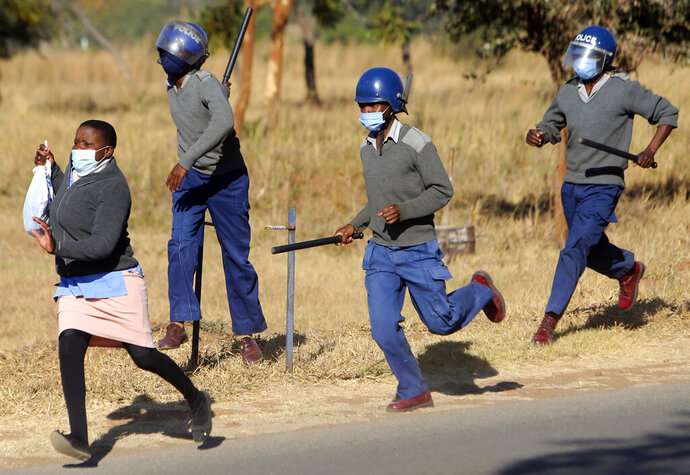 Riot police give chase a nurse who was protesting at a government hospital in Harare, Monday, July, 6, 2020. Thousands of nurses working in public hospitals stopped reporting for work in mid-June, part of frequent work stoppages by health workers who earn less than $50 a month and allege they are forced to work without adequate protective equipment. On Monday, dozens of nurses wearing masks and their white and blue uniforms gathered for protests at some of the country's biggest hospitals in the capital, Harare, and the second-largest city of Bulawayo.(AP Photo/Tsvangirayi Mukwazhi)