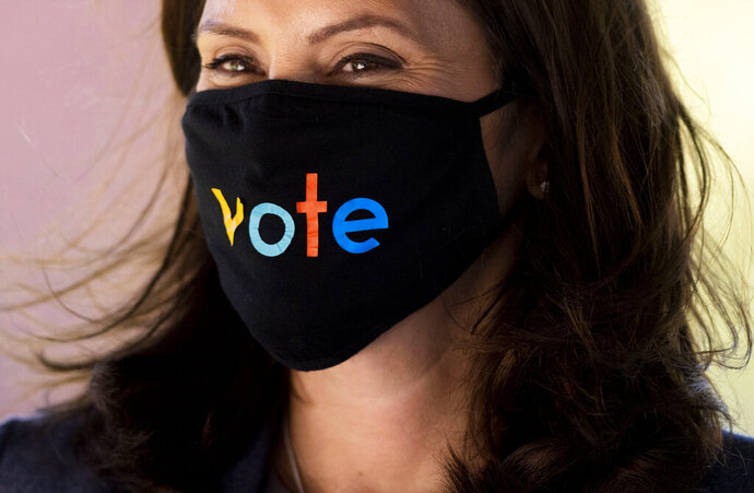 FILE - In this Oct. 7, 2020, file photo, Michigan Gov. Gretchen Whitmer wears a mask with the word