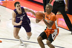 Illinois guard Adam Miller shoots as Northwestern's guard Ryan Greer (2) attempts to block in the first half of an NCAA college basketball game Tuesday, Feb. 16, 2021, in Champaign, Ill. (AP Photo/Holly Hart)