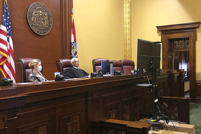 In this June 15, 2020, photo provided by the Supreme Court of Missouri, Supreme Court Clerk Betsy AuBuchon, left, and Chief Justice George W. Draper III watch remote arguments from a video monitor stacked on boxes in the state Supreme Court chambers in Jefferson City, Mo. The chief justice was the only judge in the courtroom. The other six judges and the two attorneys arguing the case all appeared using remote technology because of coronavirus precautions. (Beth S. Riggert/Supreme Court of Missouri via AP)