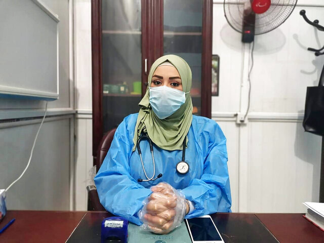 This May 13, 2020, picture provided by Dr. Marwa al-Khafaji shows the doctor back at work after 20 days in isolation after she tested positive for the coronavirus at a hospital in Karbala, Iraq. Dr. Marwa al-Khafaji's homecoming from a hospital isolation ward was tainted by spite. Someone had barricaded her family home's gate with a concrete block.  The message from the neighbors was clear: She had survived coronavirus, but the stigma of having had the disease would be a more pernicious fight. (AP Photo)