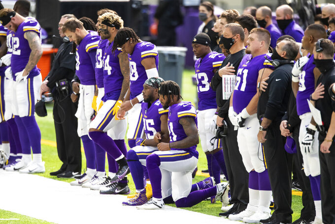 Minnesota Vikings running back Alexander Mattison (25) and Ameer Abdullah kneel during the National Anthem before the start of an NFL football game against the Tennessee Titans, Sunday, Sept. 27, 2020, in Minneapolis. The Titans defeated the Vikings 31-30. The NFL says the Tennessee Titans and Minnesota Vikings are suspending in-person activities after the Titans had three players test positive for the coronavirus, along with five other personnel. The league says both clubs are working closely with the NFL and the players' union on tracing contacts, more testing and monitoring developments. The Titans are scheduled to host the Pittsburgh Steelers on Sunday. (AP Photo/David Berding)