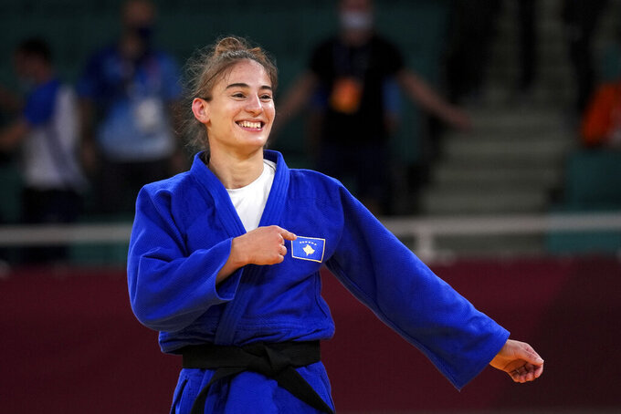 Nora Gjakova of Kosovo celebrates after defected Sarah Leonie Cystique of France in their women's -57kg judo final match, at the 2020 Summer Olympics in Tokyo, Japan, Monday, July 26, 2021. (AP Photo/Vincent Thian)