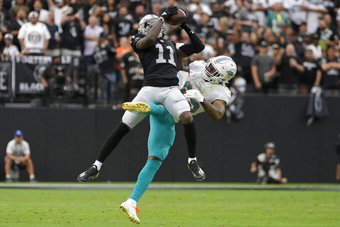 Las Vegas Raiders wide receiver Henry Ruggs III (11) makes a catch over Miami Dolphins cornerback Xavien Howard (25) during the first half of an NFL football game, Sunday, Sept. 26, 2021, in Las Vegas. (AP Photo/David Becker)