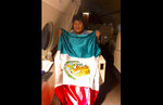 This photo released by by Mexico's Foreign Minister Marcelo Ebrard shows Bolivia's former President Evo Morales holding a Mexican flag aboard a Mexican Air Force aircraft, Monday, Nov. 11, 2019. Morales has been granted asylum in Mexico after he resigned to the presidency on Nov. 10, under mounting pressure from the military and the public after a disputed re-election victory that triggered weeks of fraud allegations and deadly protests. (Mexico's Foreign Minister via AP)