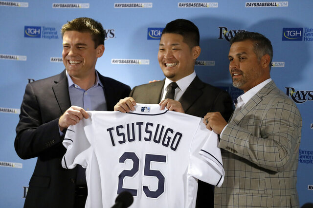 New Tampa Bay Rays baseball team outfielder Yoshitomo Tsutsugo, of Japan, center, smiles as he holds up his jersey with general manager Erik Neander, left, and manager Kevin Cash during a news conference Tuesday, Dec. 17, 2019, in St. Petersburg, Fla. Tsutsugo, 28, spent 10-seasons with the Yokohama DeNA Baystars. (AP Photo/Chris O'Meara)