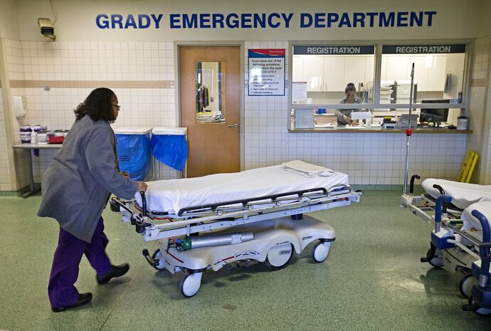 FILE-In this Friday, Jan. 24, 2014 file photo, a worker wheels beds through the emergency department at Grady Memorial Hospital, in Atlanta. Georgia's governor has issued an emergency declaration because of capacity issues at Atlanta-area hospitals after a flooding incident at the state's largest trauma center last week. Grady Memorial Hospital in Atlanta started diverting patients to other hospitals on Dec. 7 because a burst water pipe flooded and damaged multiple floors of the hospital. (AP Photo/David Goldman, File)