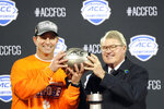 Clemson head coach Dabo Swinney, left, holds the trophy with ACC commissioner John Swofford following the Atlantic Coast Conference championship NCAA college football game against Virginia in Charlotte, N.C., Saturday, Dec. 7, 2019. Clemson won 62-17. (AP Photo/Mike McCarn)