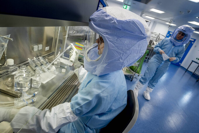 Two laboratory workers simulate the workflow in a cleanroom of the BioNTech Corona vaccine production in Marburg, Germany, during a media day on Saturday, March 27, 2021. BioNTech, the Mainz-based company that invented the messenger RNA-based vaccine, is busily ramping up its production capabilities at the company's new production facility in Marburg. BioNTech originally expected the plant could turn out 700 million doses per year; it has since upgraded its expectations to a billion a year. (AP Photo/Michael Probst)