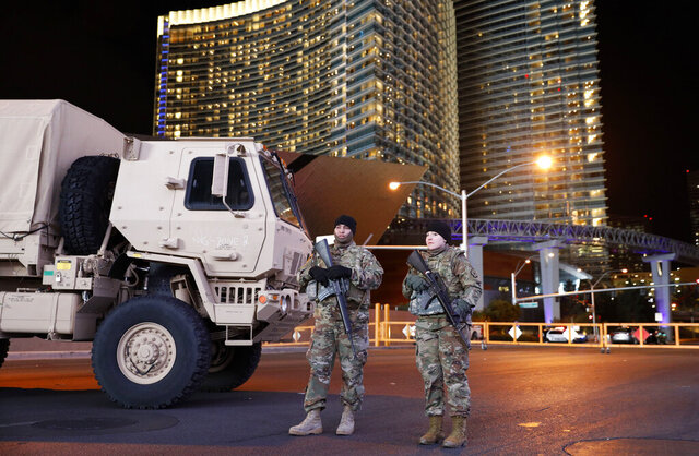 FILE - In this Dec. 31, 2018, file photo, members of the Nevada National Guard stand at a roadblock on a road leading to the Las Vegas Strip during a New Year's celebration in Las Vegas. State and federal officials are finalizing details of the role Nevada's National Guard will play in the statewide response to the coronavirus, but they're emphasizing the mission won't include enforcing martial law. The governor has activated the National Guard each New Year's Eve since the 9/11 terrorist attacks to help patrol the Las Vegas Strip. Nevada's Guard regularly is deployed overseas, but the most recent non-New Year's activation within the state was March 2017 when 140 troops responded to flooding north of Reno and President Trump approved federal disaster funding, similar to what's expected to occur now, said 1st Lt. Emerson Marcus, the Nevada Guard's historian. (AP Photo/John Locher, File)