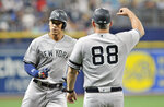 New York Yankees third base coach Phil Nevin (88) congratulates Aaron Judge, left, after Judge hit a solo home run off Tampa Bay Rays starter Brendan McKay during the first inning of a baseball game Friday, July 5, 2019, in St. Petersburg, Fla. (AP Photo/Steve Nesius)