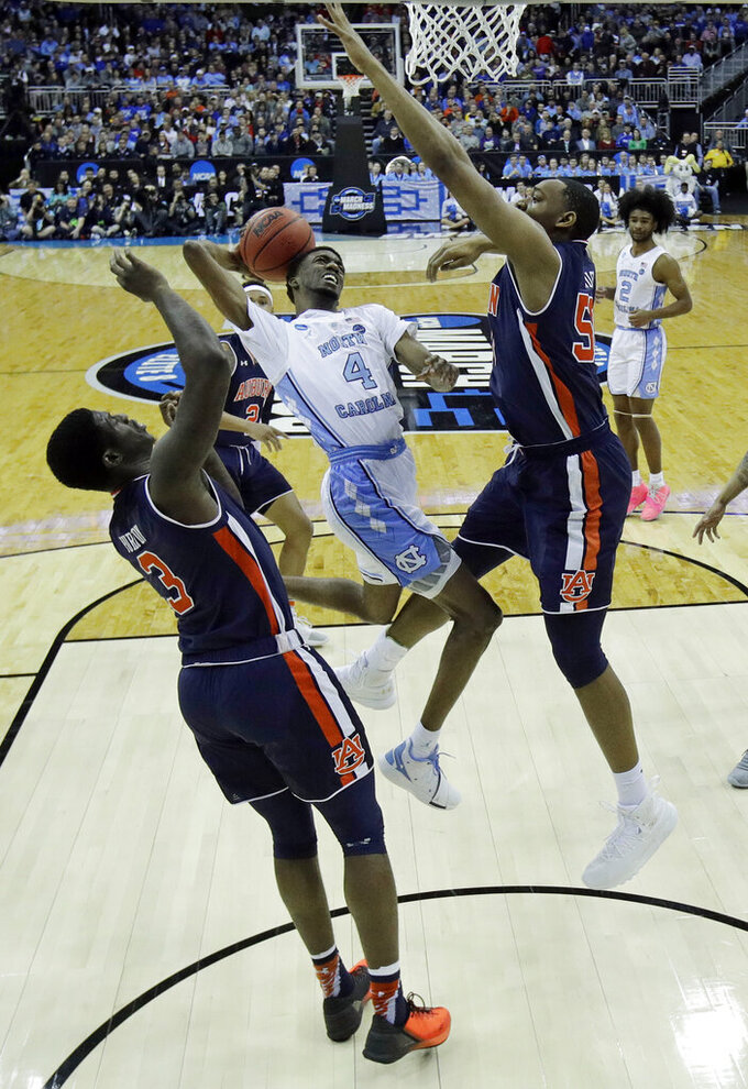 North Carolina's Brandon Robinson (4) heads to the basket as Auburn's Danjel Purifoy (3) and Austin Wiley defend during the first half of a men's NCAA tournament college basketball Midwest Regional semifinal game Friday, March 29, 2019, in Kansas City, Mo. (AP Photo/Charlie Riedel)