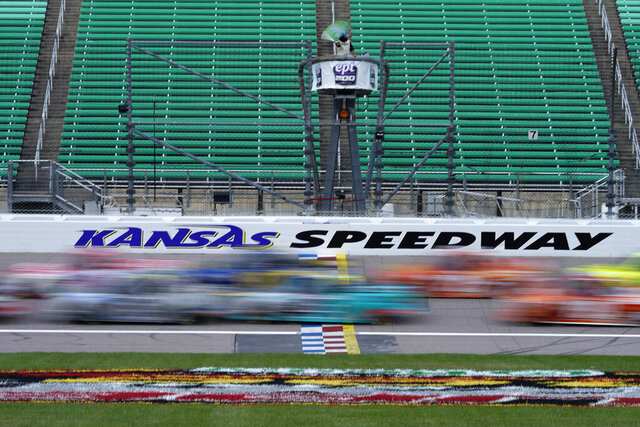 Drivers take the green flag at the start of a NASCAR Truck Series auto race at Kansas Speedway in Kansas City, Kan., Saturday, July 25, 2020. (AP Photo/Charlie Riedel)