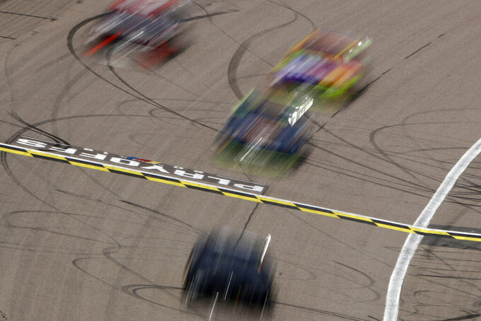 Cars are blurred by a slow shutter as they cross the start/finish line during a NASCAR Cup Series auto race at Kansas Speedway in Kansas City, Kan. Sunday, Oct. 20, 2019. (AP Photo/Charlie Riedel)