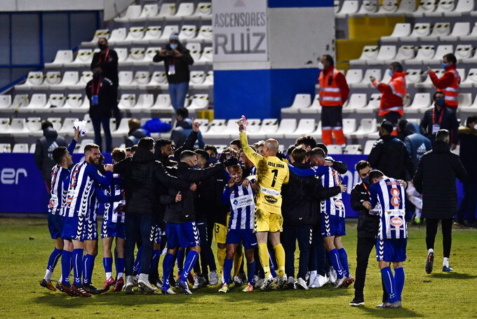 Alcoyano players celebrate after knocking out Real Madrid during a Spanish Copa del Rey round of 32 soccer match between Alcoyano and Real Madrid at the El Collao stadium in Alcoy, Spain, Wednesday Jan. 20, 2021. (AP Photo/Jose Breton)