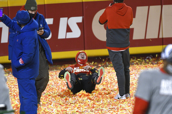 Fans celebrate on the field after the AFC championship NFL football game between the Kansas City Chiefs and the Buffalo Bills, Sunday, Jan. 24, 2021, in Kansas City, Mo. The Chiefs won 38-24. (AP Photo/Reed Hoffmann)