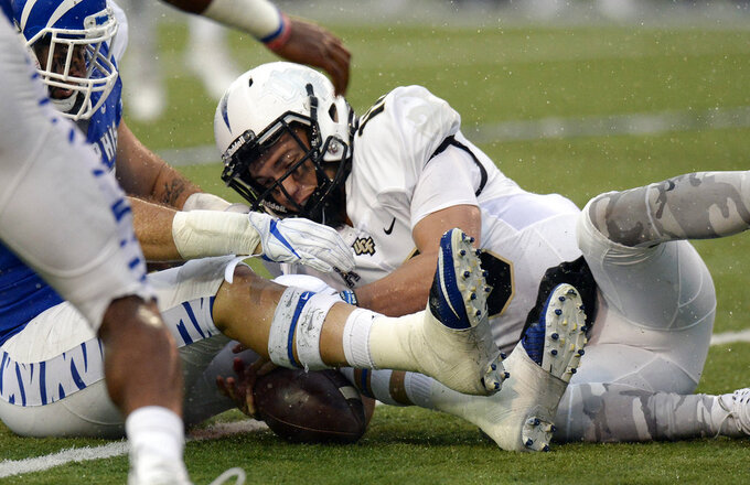 Central Florida quarterback McKenzie Milton, right, recovers his own fumble against Memphis during the second half of an NCAA college football game Saturday, Oct. 13, 2018, in Memphis, Tenn. Central Florida won 31-30. (AP Photo/Mark Zaleski)
