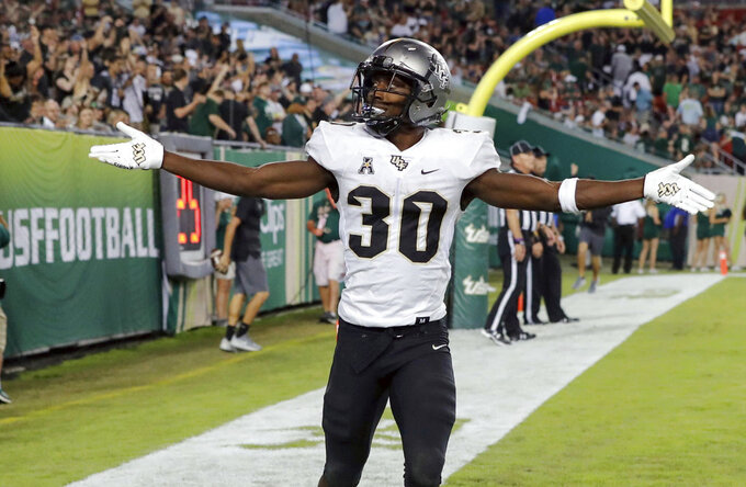 Central Florida's Greg McCrae celebrates after his third rushing touchdown against South Florida during the second half of an NCAA college football game Friday, Nov. 23, 2018, in Tampa, Fla. (AP Photo/Mike Carlson)