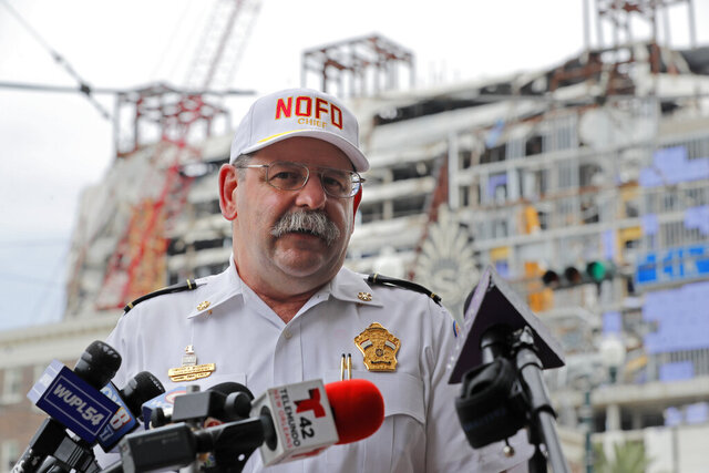 FILE - New Orleans Fire Superintendent Tim McConnell delivers an update to media for the Hard Rock Hotel building collapse site, seen in the background, in New Orleans, Monday, July 20, 2020. Contractors have not been able to recover either of two remaining bodies from the wreckage of a hotel that partly collapsed during construction last year, and they don't know when they'll be able to do so, New Orleans officials said Friday, July 24, 2020.  (AP Photo/Gerald Herbert)