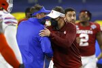Florida coach Dan Mullen, left, and Oklahoma head coach Lincoln Riley, right, meet after the Cotton Bowl NCAA college football game in Arlington, Texas, Wednesday, Dec. 30, 2020. Oklahoma won 55-20. (AP Photo/Ron Jenkins)