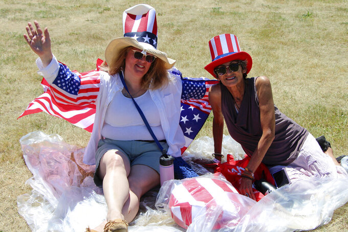 """Anna """"AJ"""" Prospect and Julie Costello of Apple Valley, Minn., were among supporters of former President Donald Trump who attended a rally organized by pillow salesman-turned conspiracy peddler Mike Lindell in New Richmond, Wis., on Saturday, June 12, 2021. Prospect says she became more politically active because of the pandemic. For a few hours last weekend, thousands of Donald Trump's loyal supporters came together under the blazing sun in a field in Western Wisconsin to live in an alternate reality where the former president was still in office — or would soon return. (AP Photo/Jill Colvin)"""